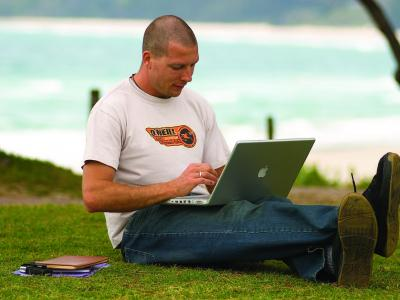 Student using his laptop at the beach! Photo credit: North Coast Institute of TAFE